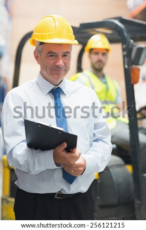 Manager standing in front of his employee in warehouse - stock photo