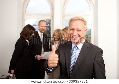Manager standing in front of his team showing thumb up - stock photo