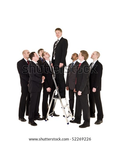 Manager standing on a step ladder with his business team around