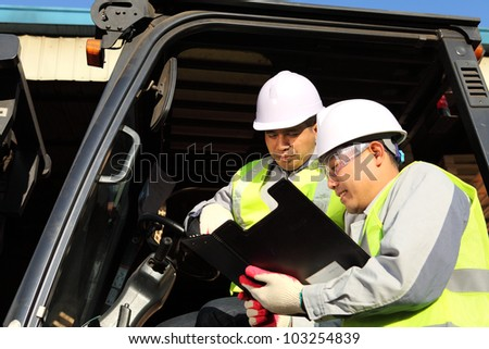 manager talking with forklift operator on warehouse - stock photo