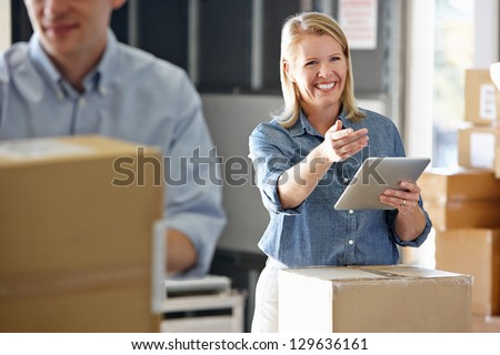 Manager Using Tablet Computer In Distribution Warehouse