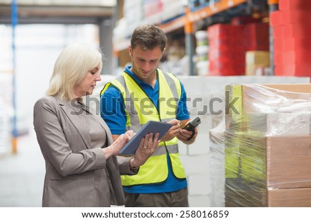 Manager using tablet while worker scanning package in warehouse - stock photo