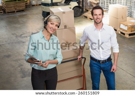 Manager walking with her colleague pulling trolleys in a large warehouse - stock photo