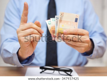 manager warns the employee while he gives him  money - stock photo