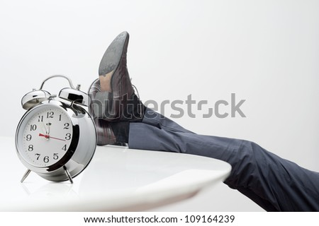 manager with feet on desk at noon - stock photo