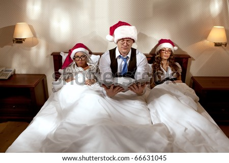 Manager with two his subordinates reading a business plan sitting in bed on New Year's night - stock photo