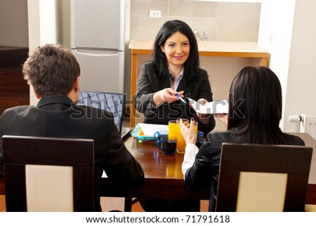 Manager woman giving an agreement to sign to a hired woman at job interview - stock photo
