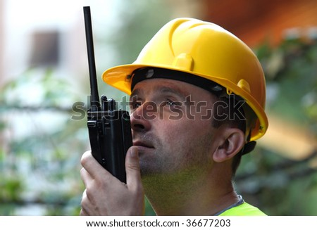 Manager/worker/architect wearing helmet and radio - stock photo