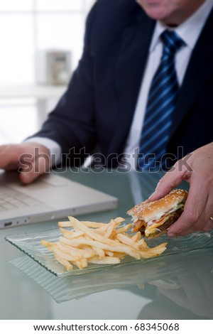 manager working and eating unhealthy food - stock photo