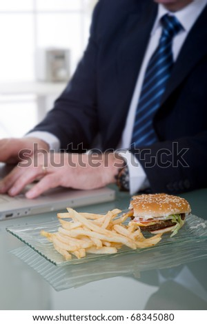 manager working and eating unhealthy food