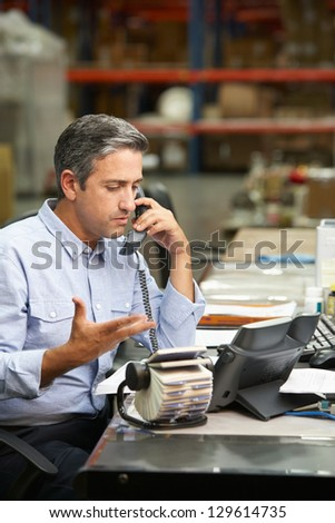Manager Working At Desk In Warehouse - stock photo