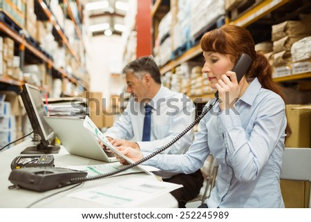 Manager working on laptop and talking on phone at desk in a large warehouse - stock photo