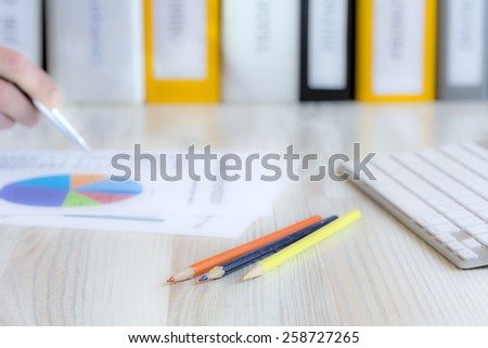 Manager working on presentation. Side view of desk with keyboard, pencils, papers with charts and human hand keeping pen. Stack of multicolored office folders on the background. - stock photo