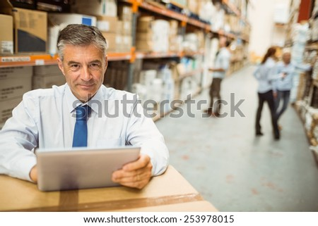 Manager working on tablet pc while looking at camera in a large warehouse - stock photo