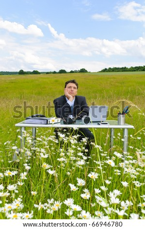 Manager works at the desk in the middle of a field of flowers against a blue sky with clouds - stock photo