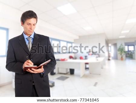 Manager writing something on his agenda - stock photo