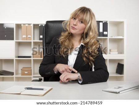 Manageress sitting at her desk in the office pointing to her watch making a point that someone is late for an interview of meeting with her - stock photo