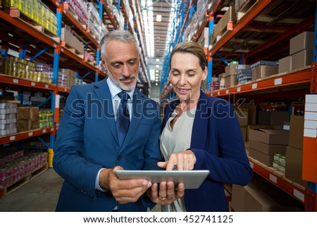 Managers are looking a tablet in a warehouse