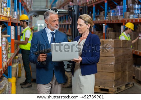 Managers are standing and looking a laptop in a warehouse