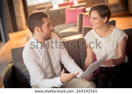 Managers discussing financial documents in a cafe - stock photo
