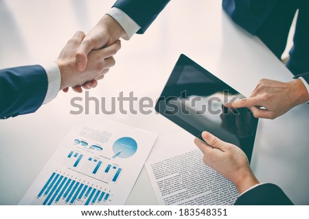 Managers shaking hands over business plans - stock photo