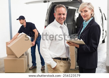 Managers smiling at camera with delivery driver behind in a large - stock photo