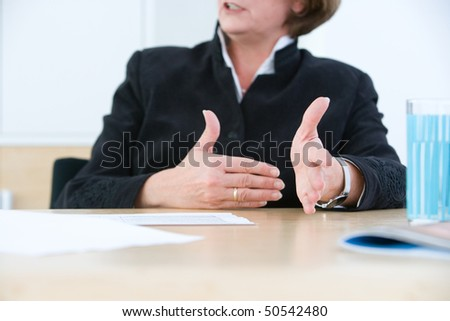 Managing woman declaims the hard facts with hands - stock photo