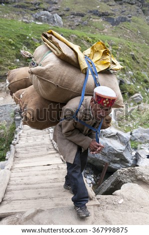 MANALI, INDIA - SEPTEMBER 09 2014: Old man carrying bags with sheeps wool crossing the bridge on September 9th 2014 in Manali, India - stock photo