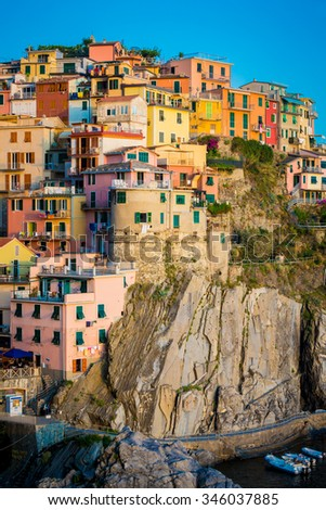 Manarola houses at sunset, hang on cliff on Cinque Terre, Italy - stock photo