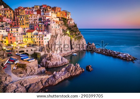 Manarola, Liguria, Italy. The wonderful Manarola village as you can see it from the mountain above. Quiet sky and peaceful sea, during sunset. - stock photo