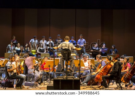 MANAUS, BRAZIL, MARCH 21: Orchestra conductor at work with music school students repeating their daily musical session at the Amazon Theatre. Manaus, Amazonas Brazil 2015 - stock photo
