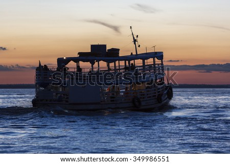 MANAUS, BRAZIL, MARCH 25: Silhouette of typical wooden Amazon boat sailing on Rio Negro near Manaus with sunset. Amazonas State. Brazil 2015