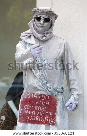 MANAUS, BRAZIL, MARCH 21: Street artist playing disguised as a white statue with front wooden sign and begging in the street of Manaus. Brazil 2015 - stock photo