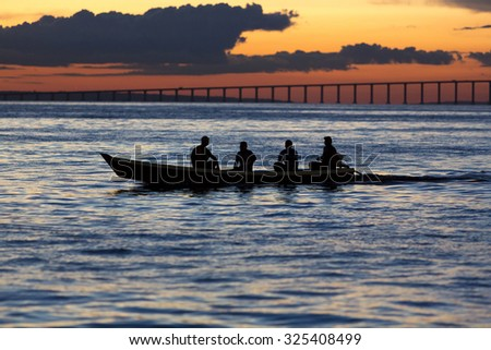 MANAUS, BRAZIL, MARCH 26: Sunset and silhouettes of people sitting on a small wooden boat and cruising on the Amazon River with the Manaus-Iranduba Bridge in the background, Brazil 2015