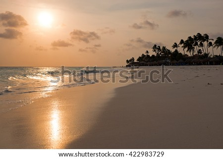 Manchebo beach on Aruba island at sunset in the Caribbean - stock photo
