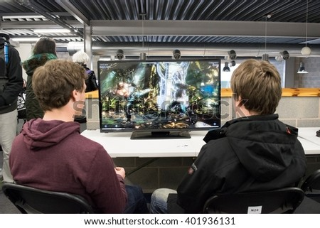 MANCHESTER, ENGLAND - APRIL 2, 2016: Visitors playing Mortal Kombat on the XBOX One at the Manchester Anime and Gaming Convention - stock photo