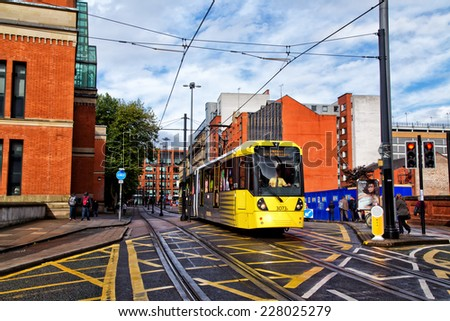 MANCHESTER,ENGLAND- OCTOBER 8,2014: A tram on the Metrolink light rail system passes the law courts on its way to Piccadilly Station. - stock photo