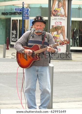MANCHESTER, ENGLAND - SEPTEMBER 25: One Man Band Busker entertaining shoppers on September 25, 2010 in Manchester, England. Buskers in Manchester are becoming much more common recently. - stock photo
