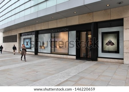 MANCHESTER, UK - APRIL 22: Shoppers walk past Louis Vuitton on April 22, 2013 in Manchester, UK. Forbes says that LV was the most powerful luxury brand in the world in 2008 with $19.4bn USD value. - stock photo