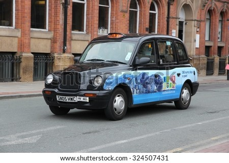 MANCHESTER, UK - APRIL 22, 2013: Taxi cab drives in Manchester, UK. There are 242,200 taxi and private hire licences in England (as of March 2015).