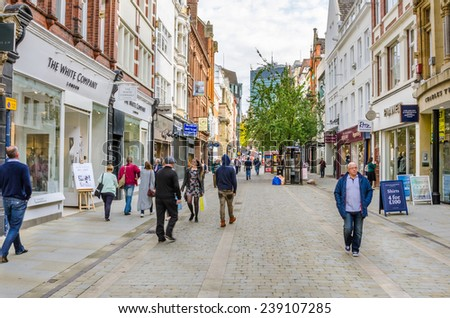 Manchester, Uk - October 3, 2014: Shoppers and tourists strolling around King Street on a warm autumn day. King Street (along with Bridge St.) is considered Manchester's most upmarket shopping area. - stock photo