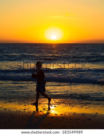 MANCORA, PERU - AUGUST 17, 2013: Unidentified boy walking on the beach at sunset on August 17, 2013 in Mancora, Peru. Mancora is a popular travel destination both for Peruvian and foreign tourists. - stock photo
