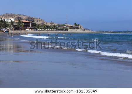 MANCORA, PERU - OCTOBER 4, 2013: Unidentified people on the beach and in the water on a sunny day on October 4, 2013 in Mancora, Peru. Mancora is a popular beach town in Northern Peru.   - stock photo