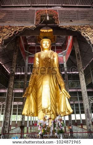 Mandalay, Burma - 2016, December 24 : A golden standing buddha halfway up the Mandalay Hill in Mandalay in central Myanmar