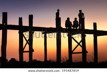 Mandalay, Myanmar 2012, A silhouette group of man chatting on U Bein Bridge on November 28th, 2012, Amarapura, Mandalay, Myanmar. U Bein Bride,  is a crossing that spans the Taungthaman Lake.