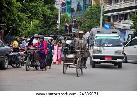 MANDALAY, MYANMAR - CICRA OCTOBER 2014: People, cars and bikes on the streets in the center of the Mandalay, Myanmar (Burma). - stock photo