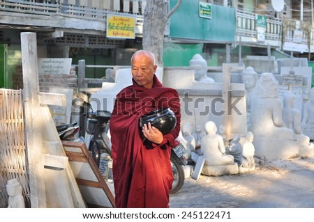 MANDALAY, MYANMAR - CIRCA OCTOBER 2014: Buddhist monk walking for alms in the morning on the background of the store with statues of the Buddha in Mandalay, Myanmar (Burma).