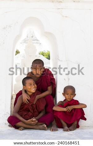 MANDALAY, MYANMAR-DECEMBER 17 : Young novice Budhist monks at white pagoda,  Myatheindan pagoda in Mingun on December 17, 2014 in Mandalay Myanmar.