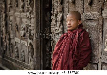 MANDALAY, MYANMAR-FEB 3, 2016 : Burmese novice standing in front of the old wood carving door at Shwenandaw Kyaung Temple, Mandalay, Myanmar - stock photo