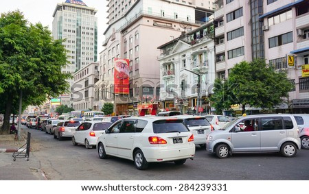 MANDALAY, MYANMAR - JAN 15, 2015. People, cars and bikes on the streets in the center of the Mandalay, Myanmar (Burma). - stock photo